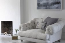 13 a grey overstuffed chair and pillows by the fireplace is one of the comfiest places to read in