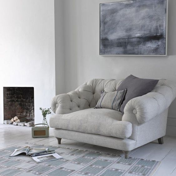 a grey overstuffed chair and pillows by the fireplace is one of the comfiest places to read in