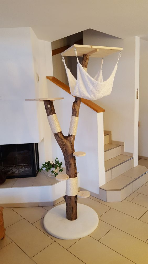 a traditional cat tree of a trunk piece plus little platforms and a platform with a hammock hanging down