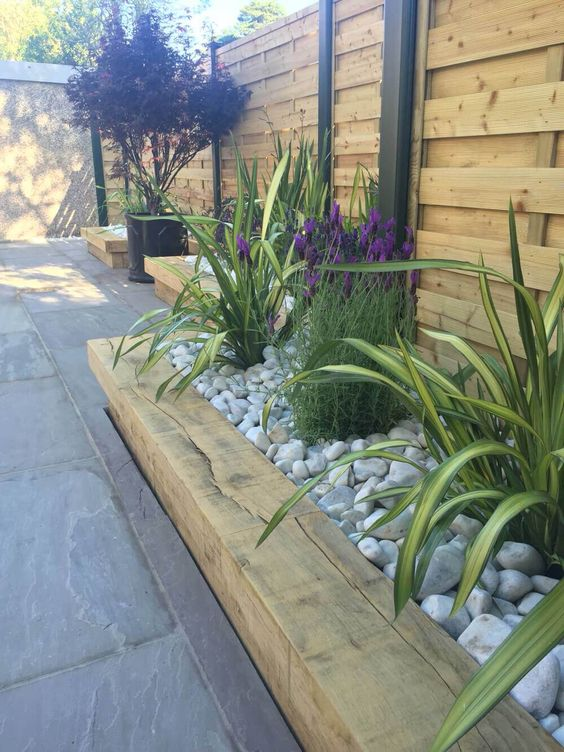 a wooden garden bed edge, bright flowers and greenery all covered with neutral pebbles on top