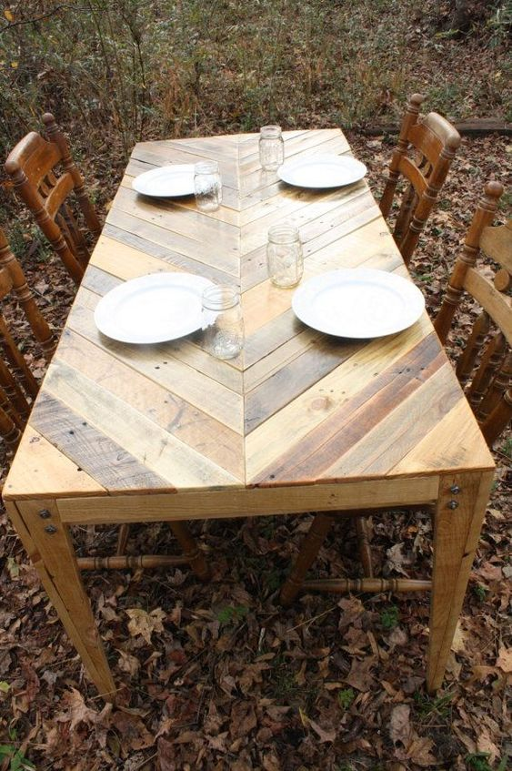 an outdoor dining table with a chevron pattern on the tabletop fully built of pallet wood and vintage chairs