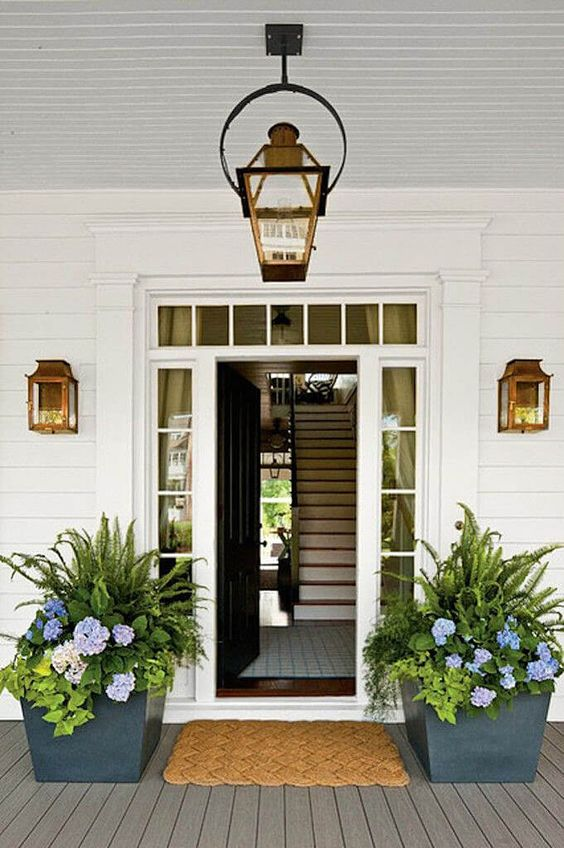 graphite grey planters with lush greenery and bright blooms line up the door and give the porch a fresh feel