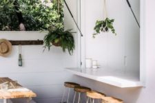 14 a garage-style window with a minimalist sleek tabletop and some wooden and metal stools
