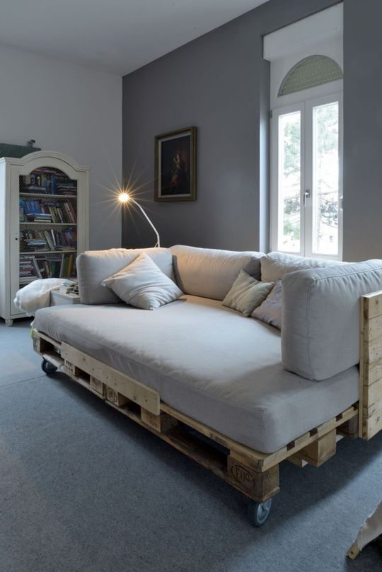 a pallet daybed with a back and casters, fitted with a comfy mattress and pillows on top