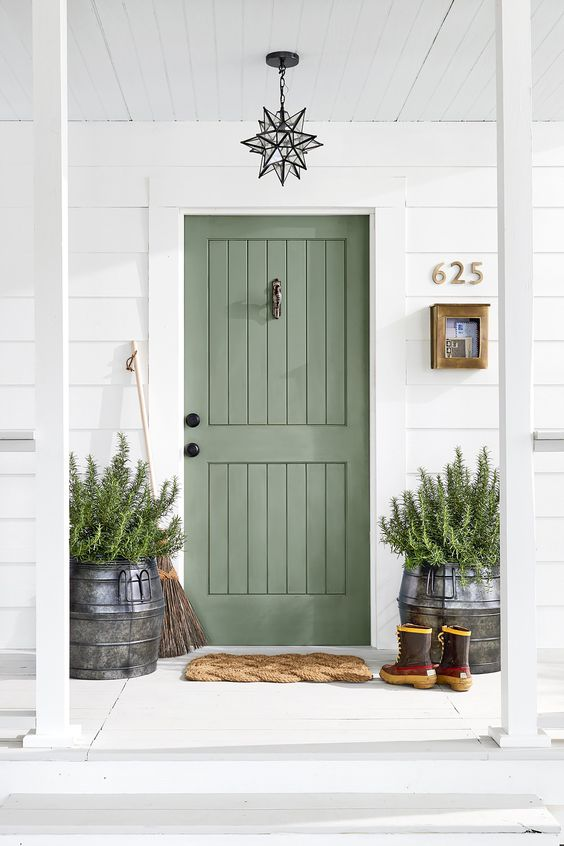 a sage green door matches the greenery that is growing in the large milk churns