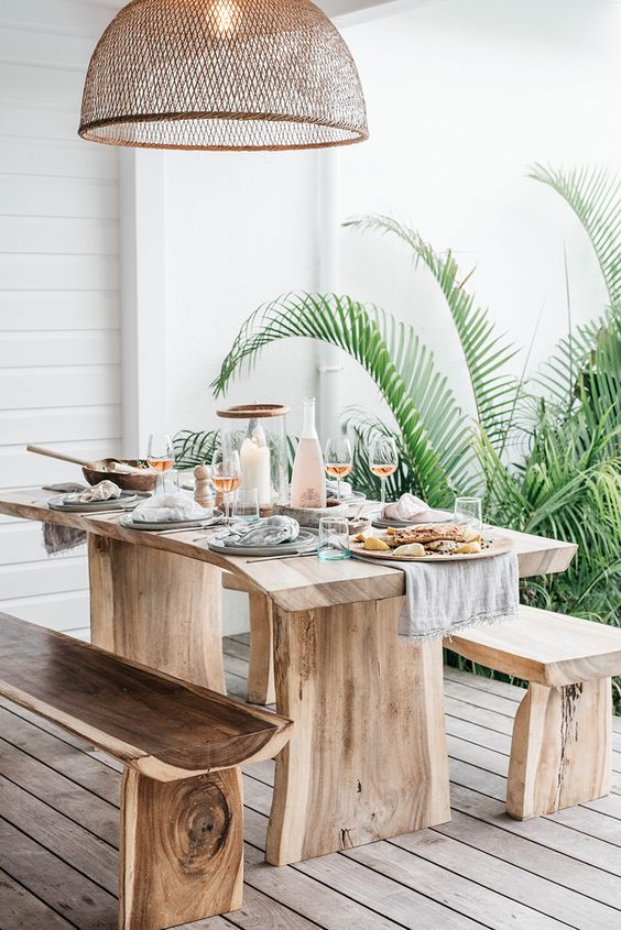 a tropical outdoor dining space with rough wooden furniture, a wicker lampshade and potted greenery