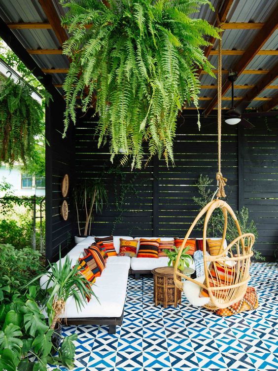 a beautiful tropical patio with a roof and greenery hanging down, with an L-shaped sofa with colorful pillows, a rattan chair and a mosaic tile floor