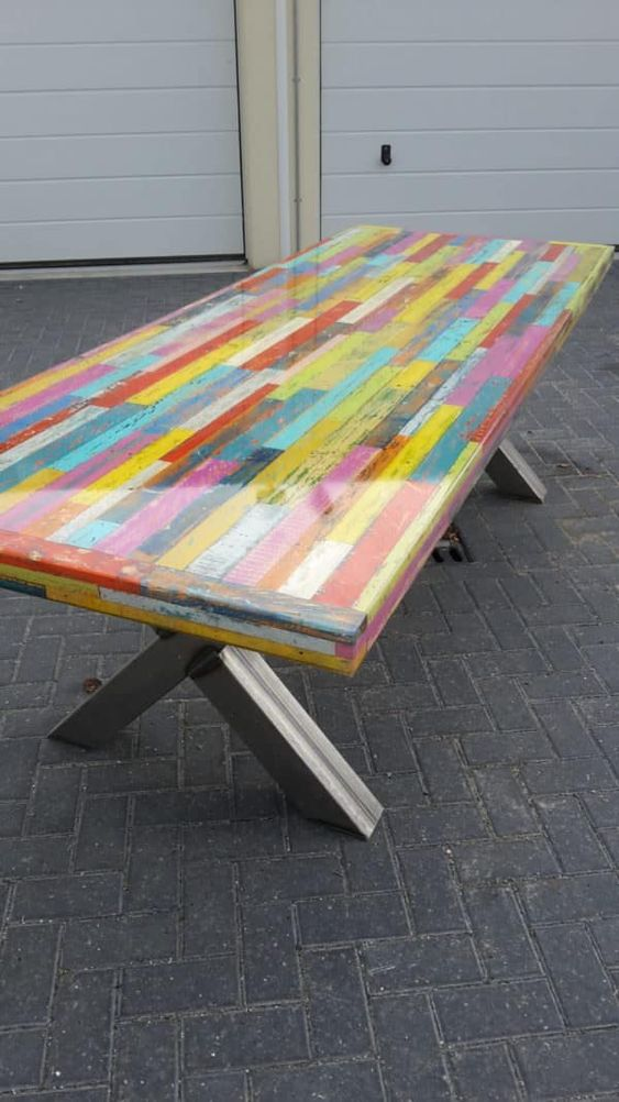 a colorful pallet dining table with a resin tabletop and comfy trestle legs is a unique idea