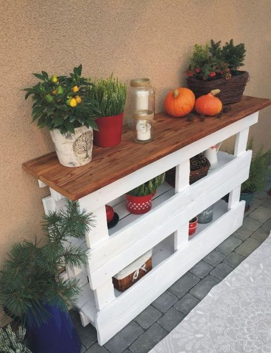 a cozy rustic console table made of two pallets in white and a stained wooden tabletop looks cool