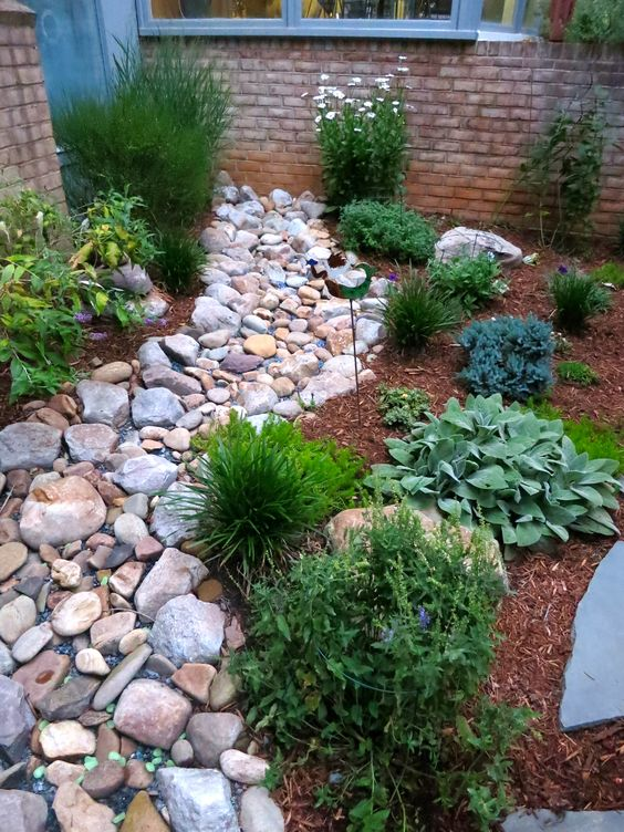 a dry stream idea with large pebbles and rocks plus green grasses around and some blooms