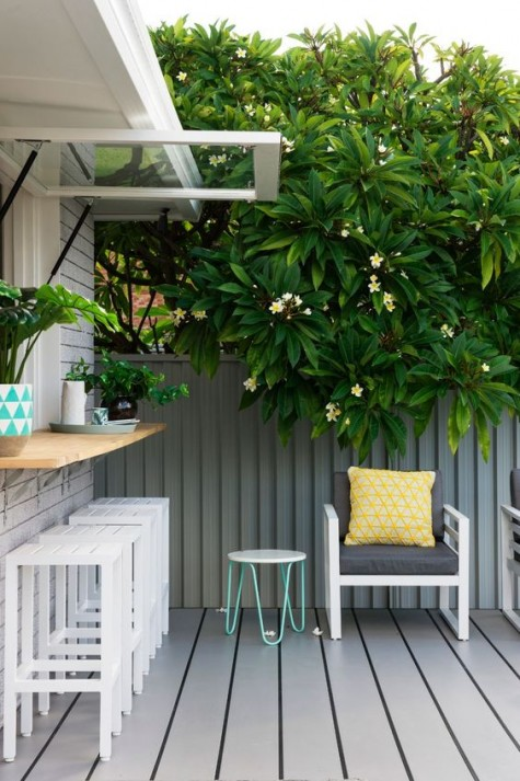a garage-style window with a wooden windowsill outdoors, white plank stools and a grey wooden deck