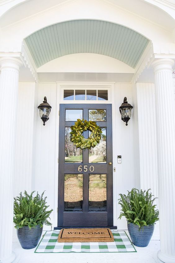 a navy door with glass, navy patterned planters with ferns and vintage lamps over the pots