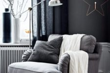 15 a simple grey upholstered chair by the window, a metal floor lamp, pillows and a knit blanket