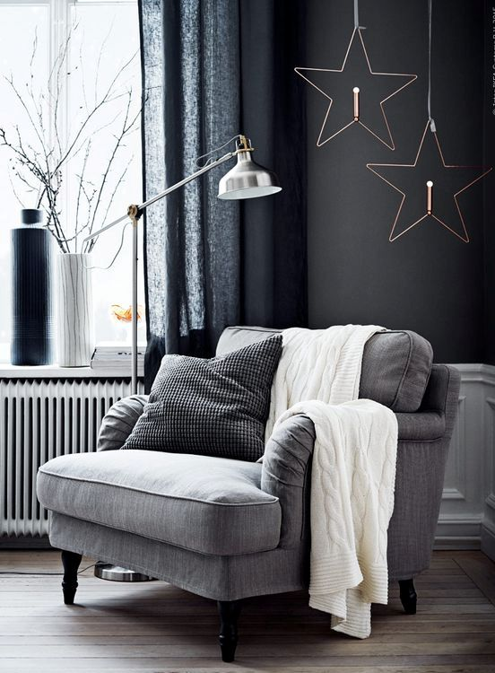 a simple grey upholstered chair by the window, a metal floor lamp, pillows and a knit blanket