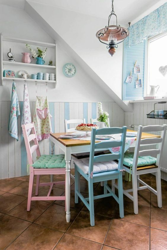 a vintage-inspired dining nook with pastel chairs of the same design and touches of powder blue