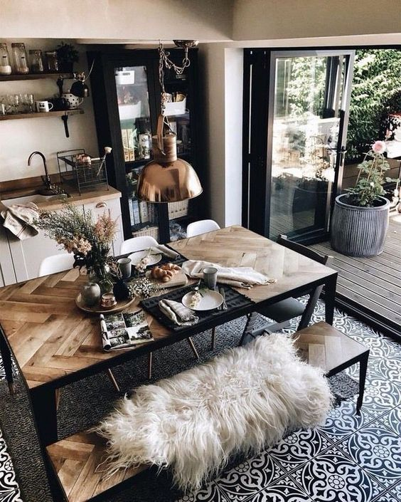 a gorgeous dining table with a chevron clad tabletop of pallet wood and black metal framing and matching benches for a boho space