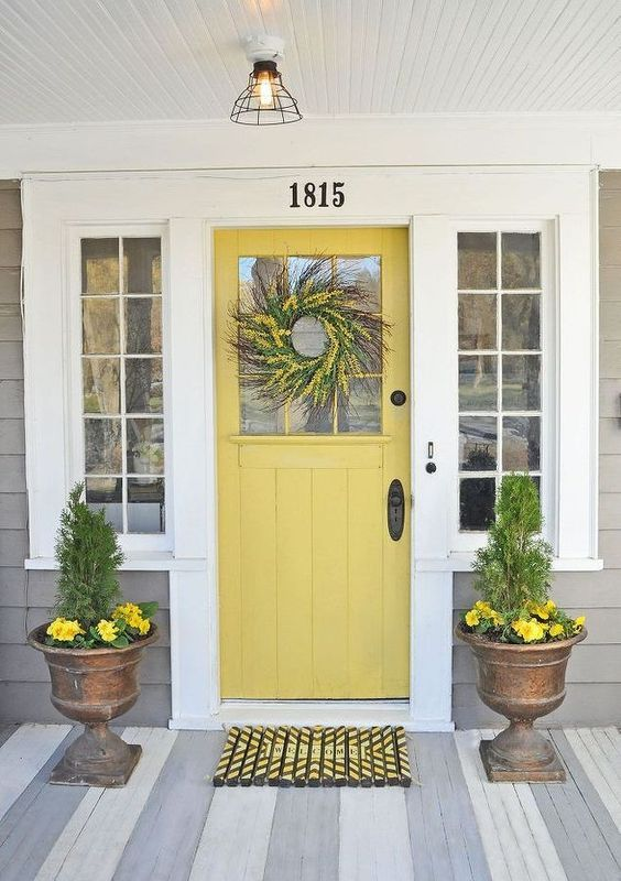 a mustard farmhouse door, antique stone urns with greenery and yellow blooms to match the door