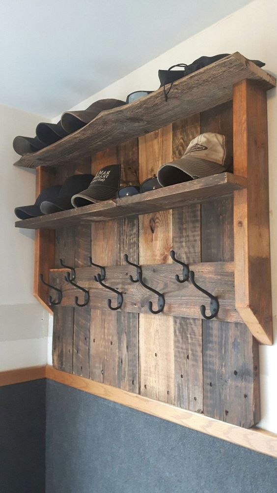 a stained wood pallet rack with space for caps and hats, with hooks is a great idea for an entryway
