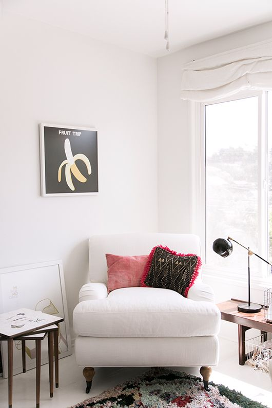 a white overstuffed chair with pillows by the window is a cool furniture piece to read on
