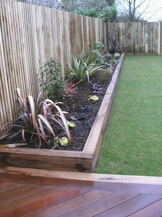 stained wood garden bed edging and matching pathways for a relaxed boho feel in your garden