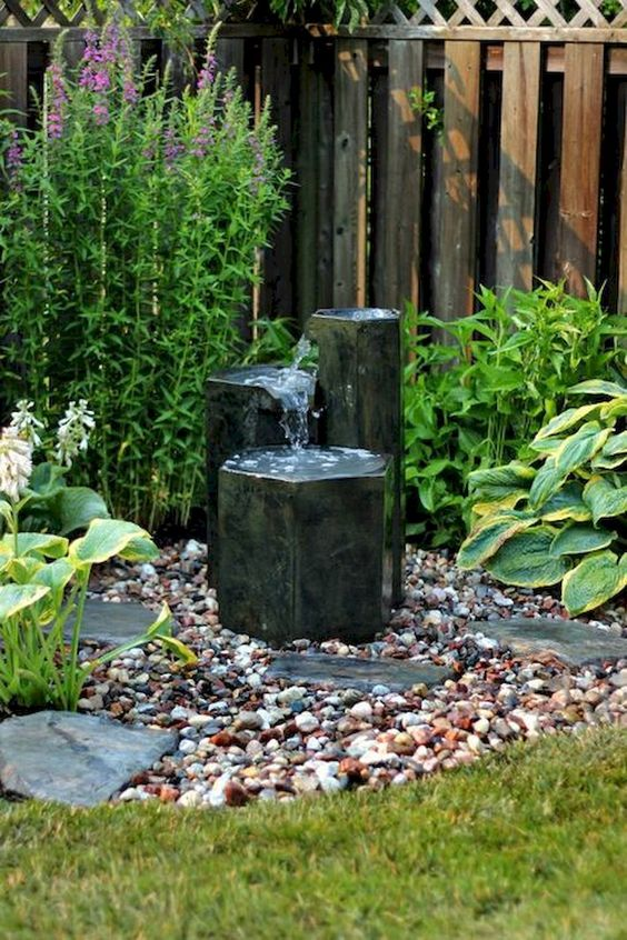 stylish black rock fountains with pebbles around will make your front yard more chic and bold