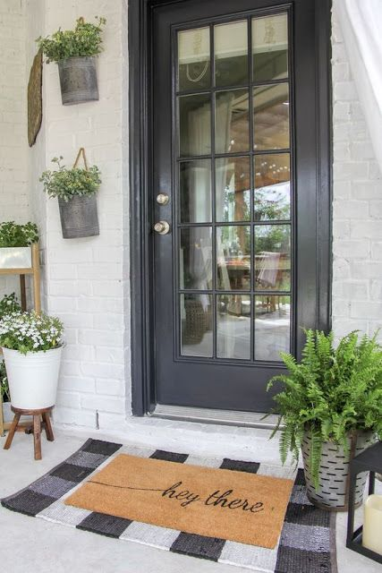 a black glass door, a buffalo plaid rug, a metal planter with fern and some planters on the wall