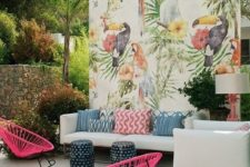 17 a colorful tropical patio with a white sofa and colorful pillows, hot pink chairs, a bright watercolor wall and little stools