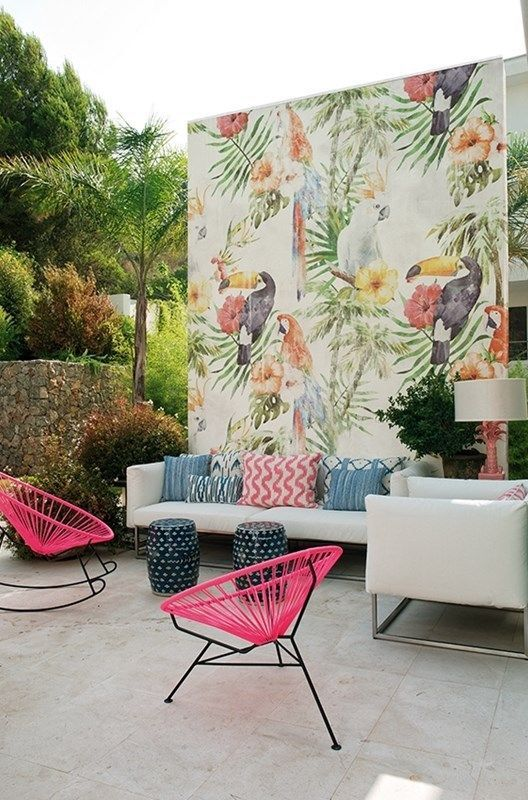 a colorful tropical patio with a white sofa and colorful pillows, hot pink chairs, a bright watercolor wall and little stools