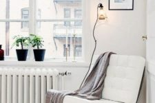 17 a comfortable contemporary chair of metal and white leather and a blanket for cozy reading