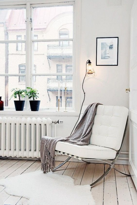a comfortable contemporary chair of metal and white leather and a blanket for cozy reading