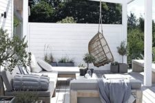 17 a welcoming summer lounge with comfortable wooden furniture and touches of concrete plus a rattan chair