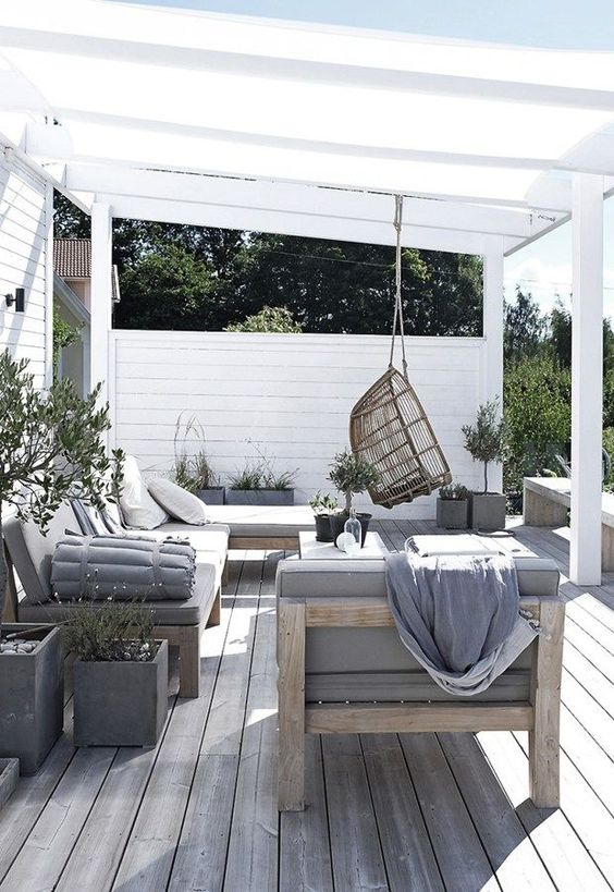 a welcoming summer lounge with comfortable wooden furniture and touches of concrete plus a rattan chair