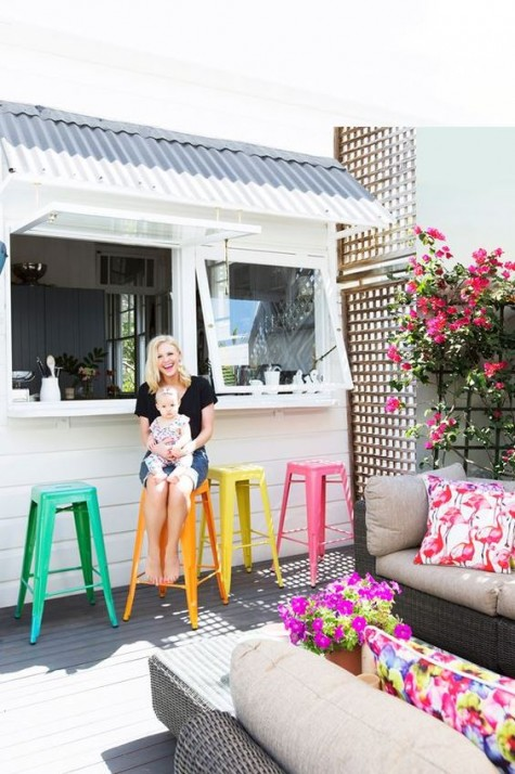 garage-style windows and a small breakfast space outdoors that is spruced up with colorful metal chairs