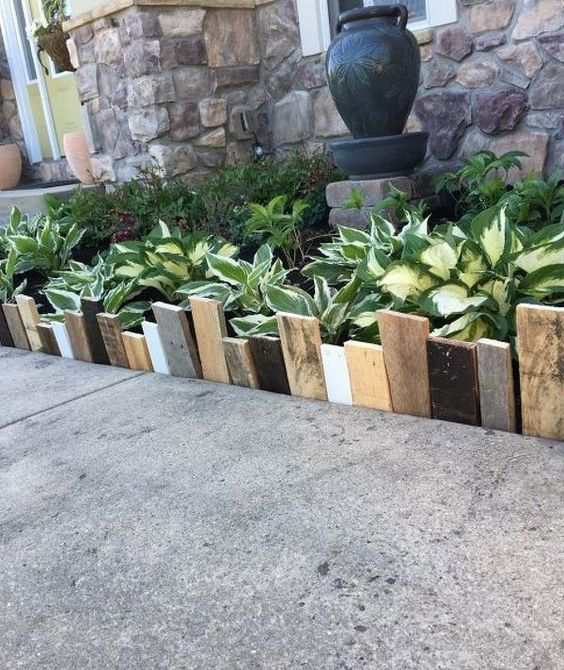 simple and catchy garden bed edging done with mismatching woodne planks in various colors