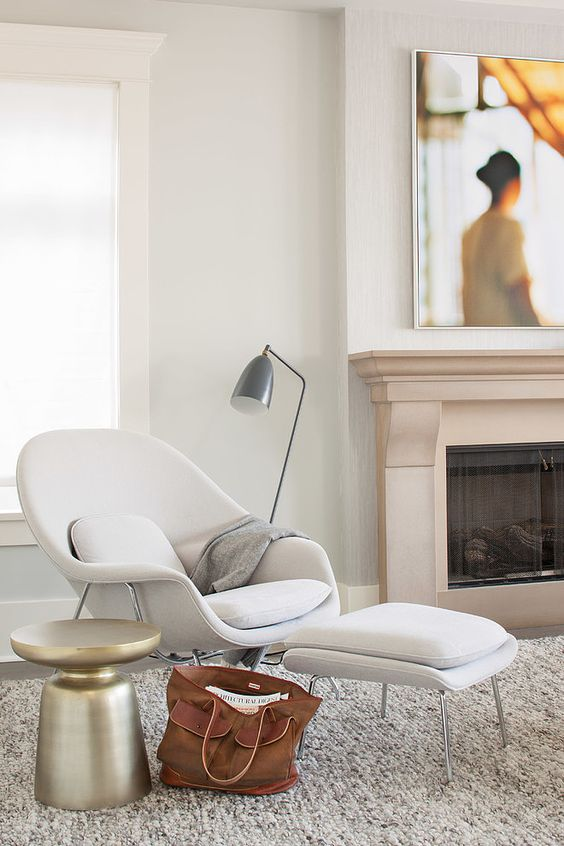 a comfy mid-century-inspired white chair and a matching footrest, a metal floor lamp and a metal side table for a comfy nook