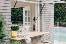 18 a garage door-styled window and an outdoor breakfast space or bar top withh white metal chairs and wooden tops