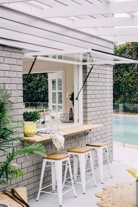 a garage door-styled window and an outdoor breakfast space or bar top withh white metal chairs and wooden tops