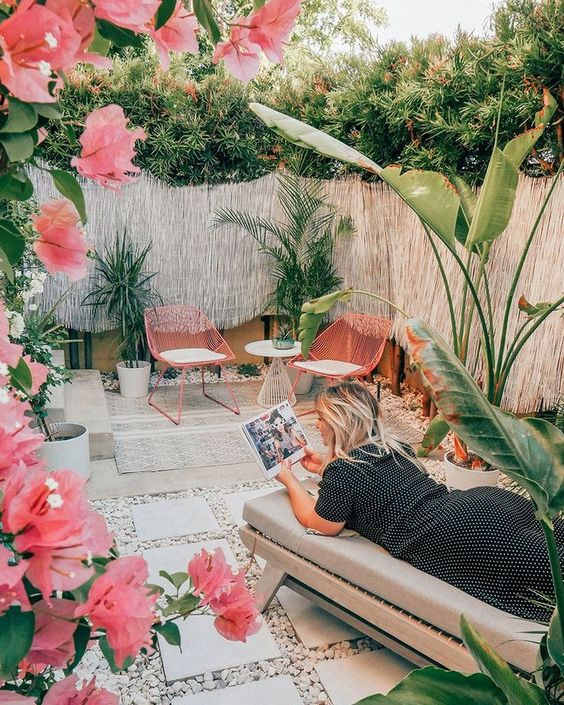 a gorgeous tropical patio with pink chairs and pink blooms, a comfy daybed, potted tropical plants