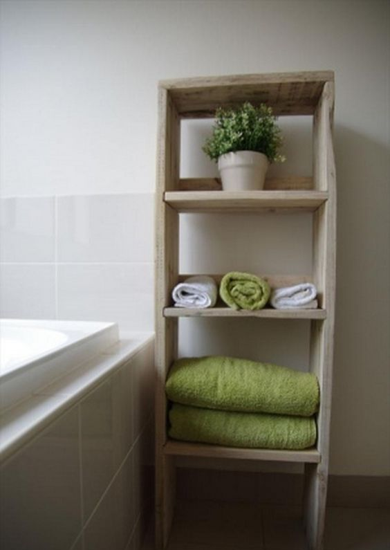 a bathroom shelving unit with several tiers for storign towels and some potted greenery built of pallets