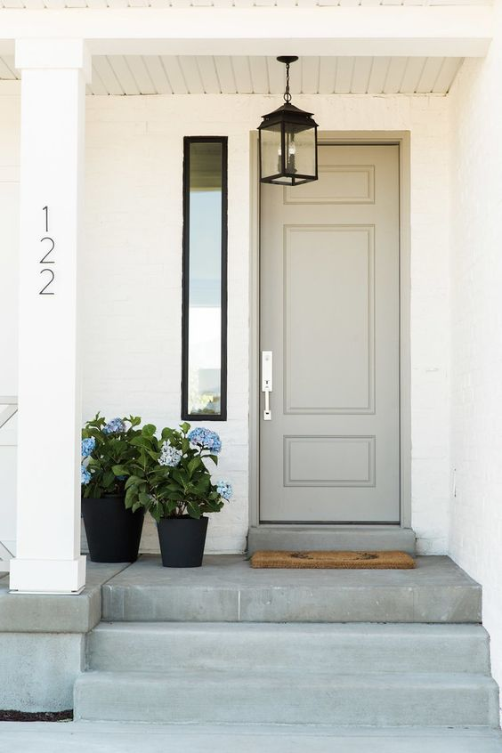 a dove grey door, a vintage lamp and a duo of black planters with blue flowers create a cozy vintage-inspired porch