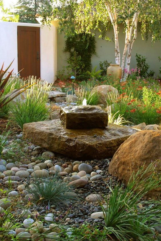 a gorgeous rock fountain looks very natural and cool in a desert garden