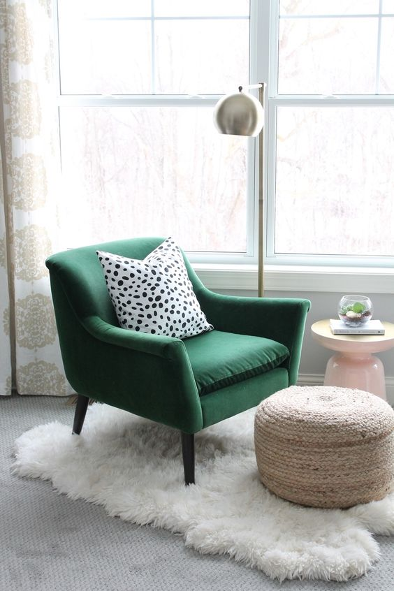 a green velvet chair with a polka dot pillow, a woven ottoman, a fur rug and a metal floor lamp