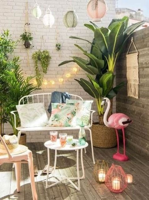 a mini tropical deck with potted greenery, a pink flamingo, colorful candle lanterns, elegant white forged furniture and lights