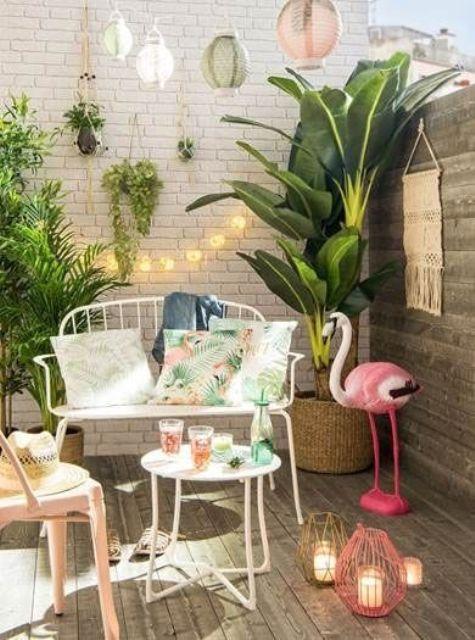 một sàn nhỏ nhiệt đới với cây xanh trong chậu, một con hồng hạc hồng, đèn lồng nến đầy màu sắc, đồ nội thất rèn màu trắng thanh lịch và đèn