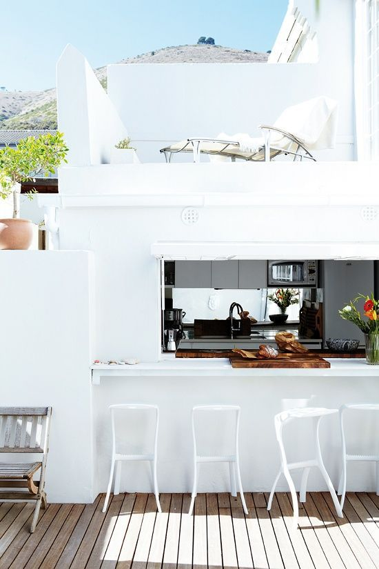 a roll up window, a white tabletop and white stools for a bright minimalist outdoor space