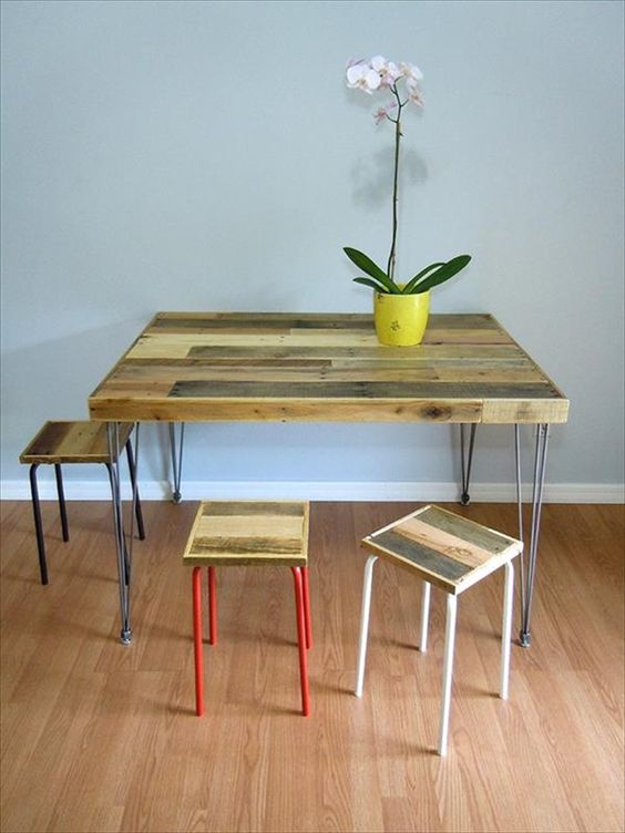 a rustic dining table with a pallet wood tabletop on hairpin legs and some matching stools