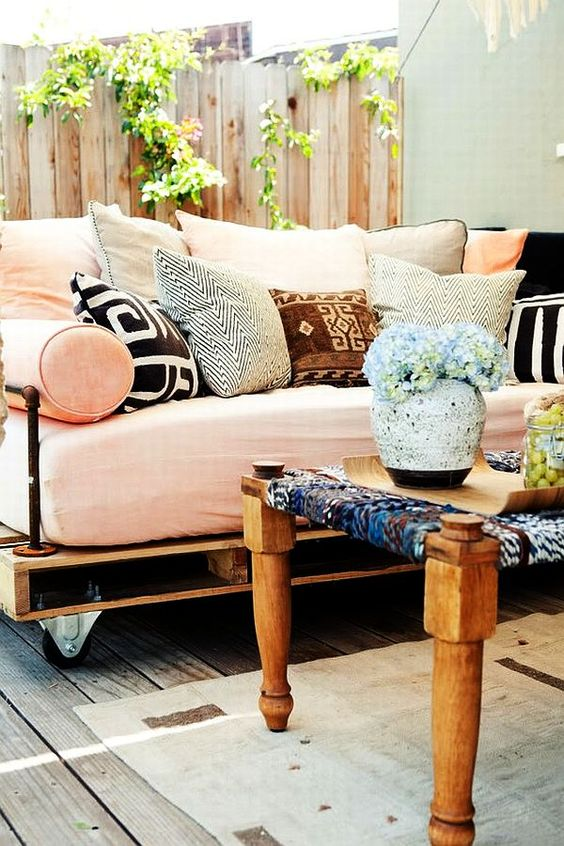 an outdoor pallet daybed on casters with a soft mattress and lots of colorful and printed pillows