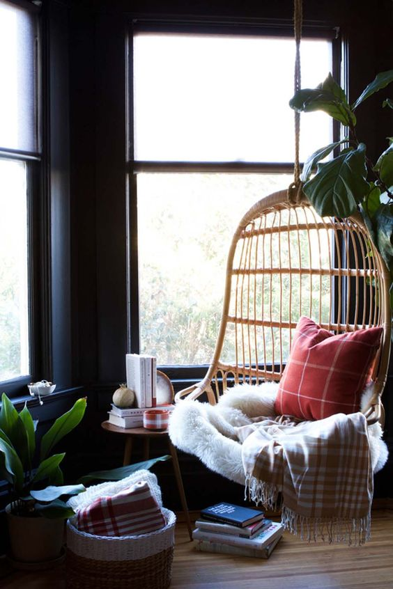 a hanging rattan birdcage chair with pillows, a blanket, a fur throw is a gorgeous base for a reading nook