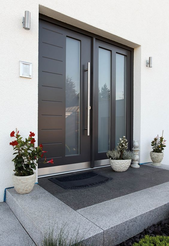 a large contemporary door with glass inserts, three planters with blooms and greenery on the porch