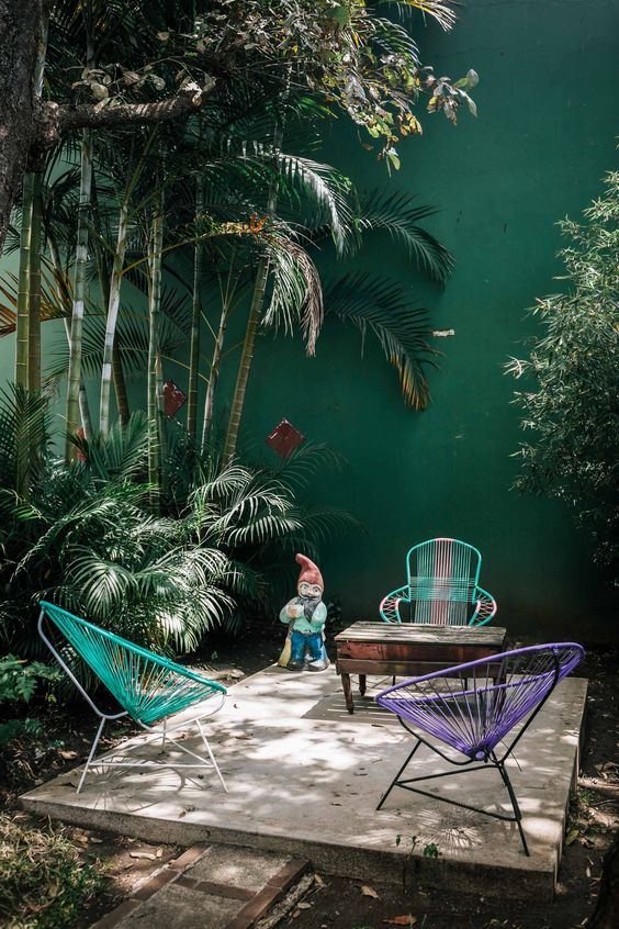 a simple tropical patio with colorful chairs, a vintage wooden table and lots of tropical plants growing aroud